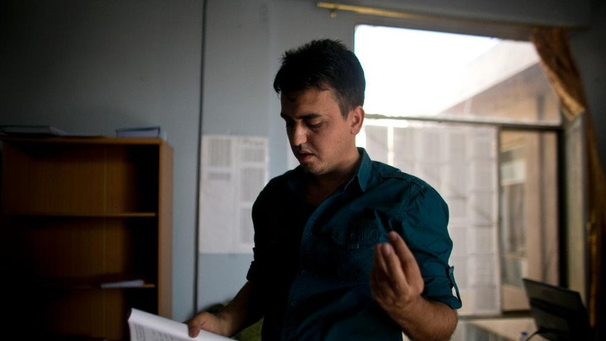 In this May 22, 2016 photo, Bahzad Farhan Murad talks to The Associated Press in the small office where he collects evidence on crimes against Yazidis, in Dohuk, northern Iraq. Murad, a 28-year-old Yazidi, is on a personal quest to collect evidence of the Islamic State group's devastating attack on his community in August 2014. He hopes his detailed files of over 2,400 victims can assist a future criminal prosecution and preserve the historical record of IS's massacre of up to 5,000 Yazidi men and enslavement of thousands of women. (AP Photo/Maya Alleruzzo)