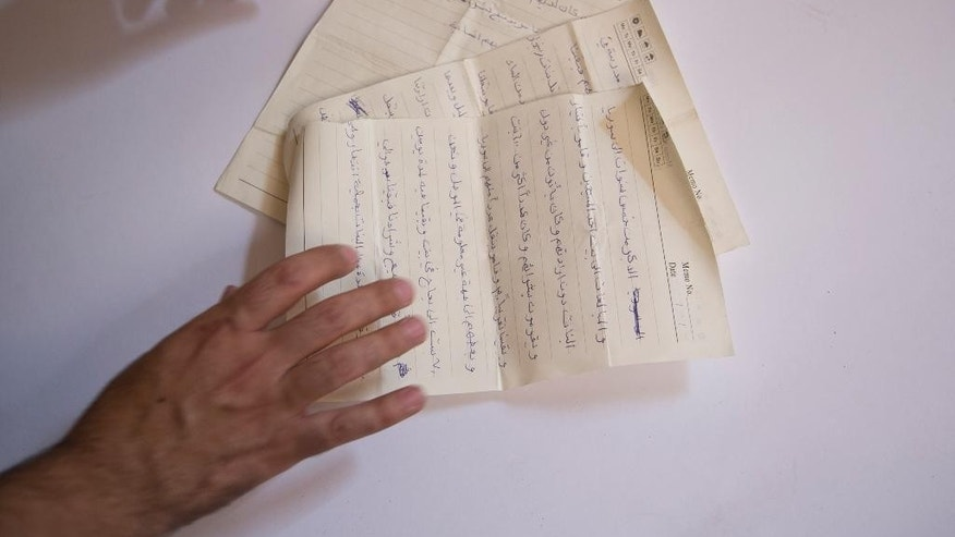 In this May 22, 2016 photo, Bahzad Farhan Murad arranges the pages of a diary written by a Yazidi girl while in Islamic State militant captivity, in Dohuk, northern Iraq. Murad, a 28-year-old Yazidi, is on a personal quest to collect evidence of the Islamic State group's devastating attack on his community in August 2014. He hopes his detailed files of over 2,400 victims can assist a future criminal prosecution and preserve the historical record of IS's massacre of up to 5,000 Yazidi men and enslavement of thousands of women. (AP Photo/Maya Alleruzzo)