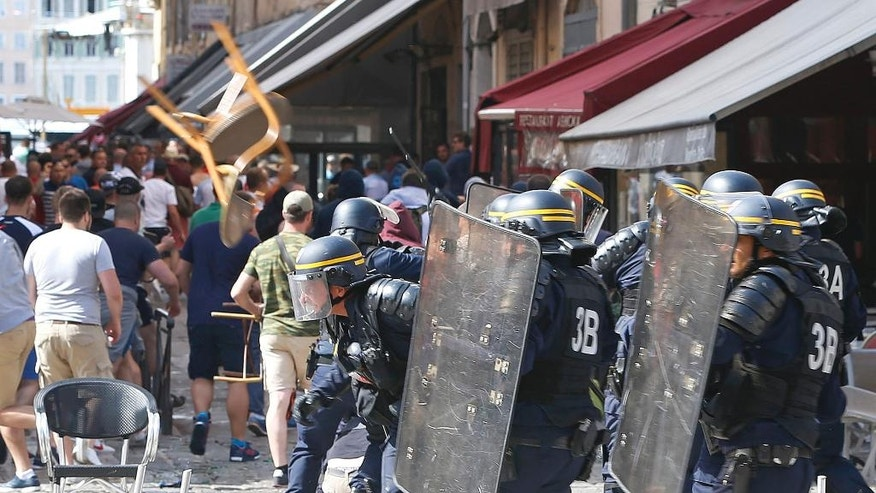 French police officers charge soccer supporters during clashes in downtown Marseille, France, Saturday, June 11, 2016. Riot police have thrown tear gas canisters at soccer fans Saturday in Marseille's Old Port in a third straight day of violence in the city.  (AP Photo/Darko Bandic)