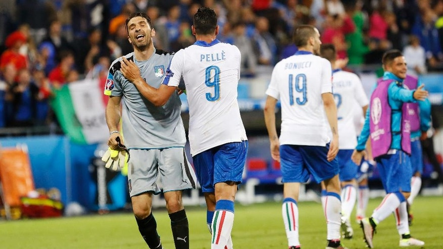 Italy's Graziano Pelle, second left, and goalkeeper Gianluigi Buffon, left, celebrate at the end of the Euro 2016 Group E soccer match between Belgium and Italy at the Grand Stade in Decines-Charpieu, near Lyon, France, Monday, June 13, 2016. (AP Photo/Laurent Cipriani)