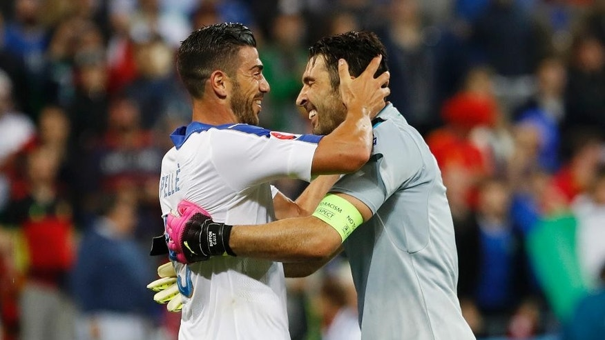 Italy's Graziano Pelle, left, and goalkeeper Gianluigi Buffon celebrate at the end of the Euro 2016 Group E soccer match between Belgium and Italy at the Grand Stade in Decines-Charpieu, near Lyon, France, Monday, June 13, 2016. (AP Photo/Laurent Cipriani)