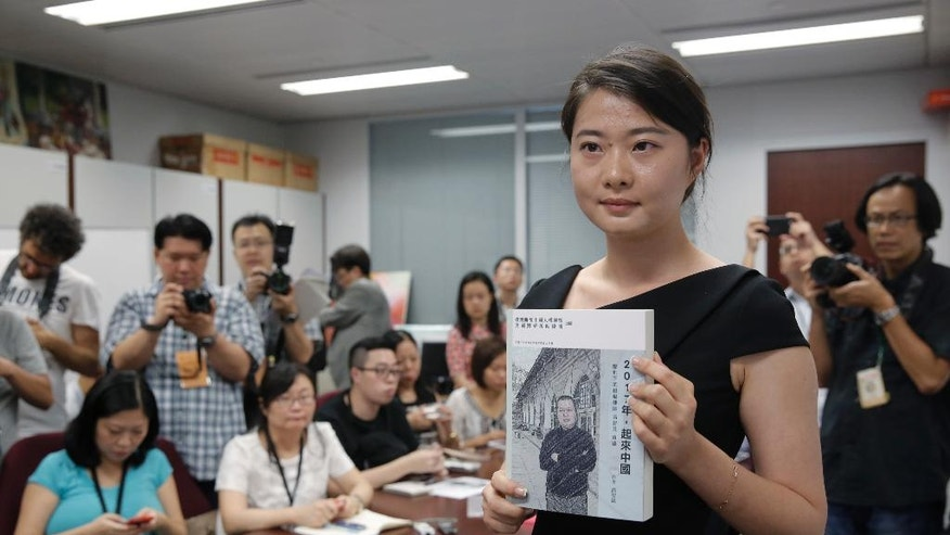 "Grace Geng, the daughter of one of China's most prominent human rights lawyers Gao Zhisheng, presents a book authored by her father at a news conference in Hong Kong, Tuesday, June 14, 2016. The book, titled ""Stand Up China 2017 - China's Hope: What I Learned During Five Years as a Political Prisoner"" is a memoir by Gao in which he details the torture he says he endured while detained and jailed as well as three years of being held in solitary confinement. Before being detained and jailed, Gao was a leading figure in the country's small community of rights lawyers and was admired for his bold defense of politically sensitive members of the banned Falun Gong spiritual movement and farmers with land disputes. (AP Photo/Kin Cheung)"