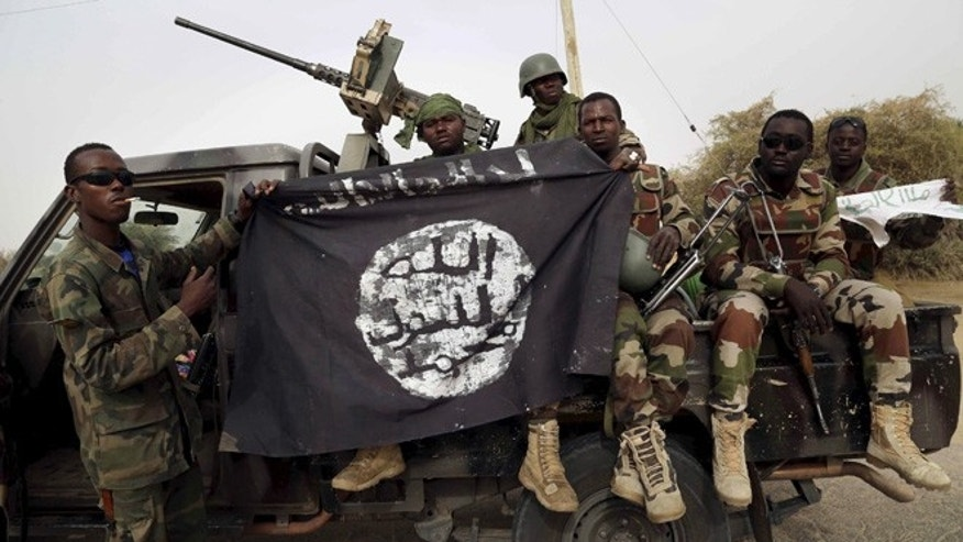 March 2015: Nigerian soldiers hold up a Boko Haram flag that they had seized in Damasak, Nigeria.