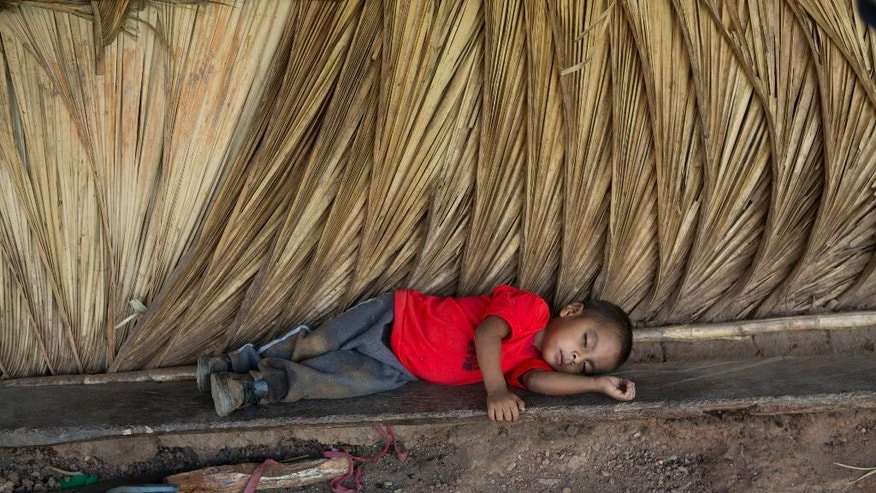In this May 31, 2016 photo, too tired to play, Giovani Martinez rests on a makeshift bench outside his home in the village of Caparrosa, in Guatemala's eastern state of Chiquimula. Historically affected by poverty, thousands of people in eastern Guatemala are suffering from a prolonged drought that has resulted in a food crisis. Many of the children are beginning to show signs of malnutrition. (AP Photo/Moises Castillo)