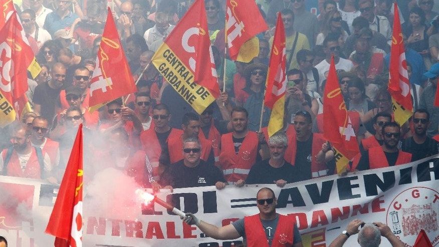 Workers hold flags and burn flares during a day of strikes and protests, in Marseille, southern France, Thursday, June 14, 2016. Workers strike across sectors of the French economy and march through French cities in what unions hope is a huge outpouring of discontent at changes to labor protections and a big challenge to the government. (AP Photo/Claude Paris)