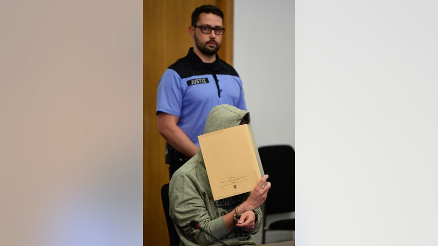 Sivio S , covers his face at  the start of his trial at regional court in Potsdam, near Berlin, on Tuesday June, 14, 2016 as he is accused of abusing and killing two boys, Elias and Mohamed, a four-year-old  refugee child he kidnapped from the chaotic grounds of Berlin's main refugee registration center LaGeSo.  (John MacDougall/Pool Photo via AP)