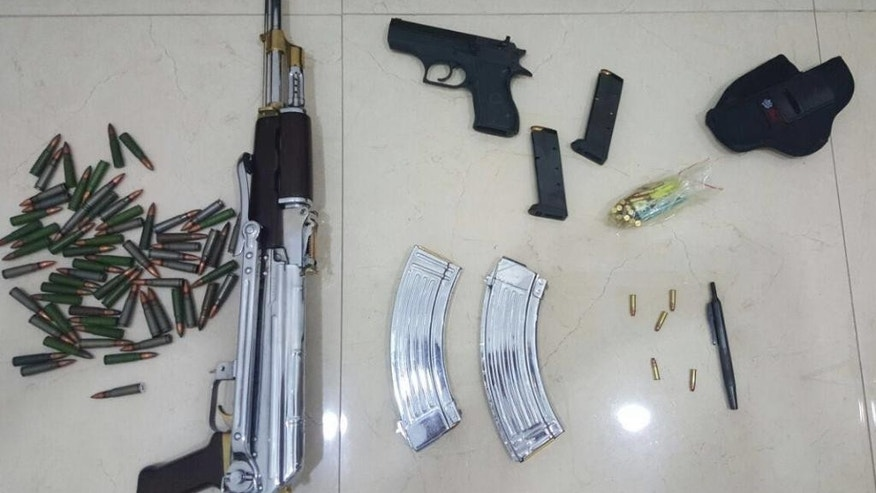 In this Tuesday, June 14, 2016 photo released by the Kuwait Ministry of Interiors, a Kalashnikov rifle, a handgun and ammunition plus a pen gun found and presented after authorities raided the home of Sheikh Athbi al-Fahad Al Sabah the former head of Kuwait's National Security Office, in Kuwait. The hunt for a renegade nephew of Kuwait's emir has turned up a gun disguised as a pen in his home, adding yet another layer of mystery to a bizarre case involving two other ruling family members and others.( Kuwait Ministry of Interiors via AP)