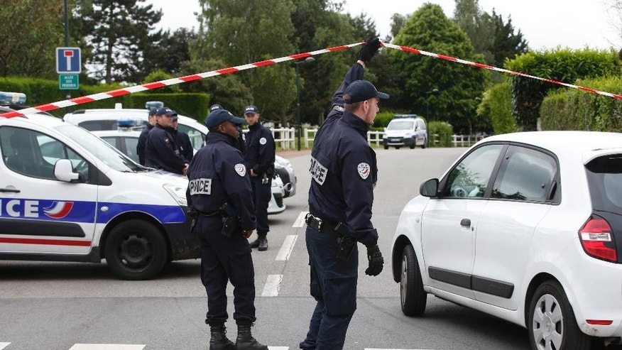 French police officers work at the crime scene the day after a knife-wielding attacker stabbed a senior police officer to death Monday evening outside his home in Magnanville, west of Paris, France, Tuesday, June 14, 2016. The attacker and a female companion of the police commander were later found dead after police commandos stormed the home and rescued the couple's three-year-old son. (AP Photo/Thibault Camus)