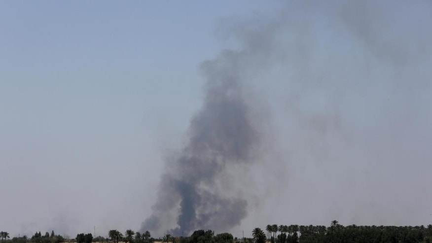 Smoke rises after airstrikes by U.S.-led coalition warplanes as Iraqi security forces advance their positions in the southern neighborhoods of Fallujah to retake the city from Islamic State militants, , Iraq, Monday, June 14, 2016. (AP Photo/Hadi Mizban)