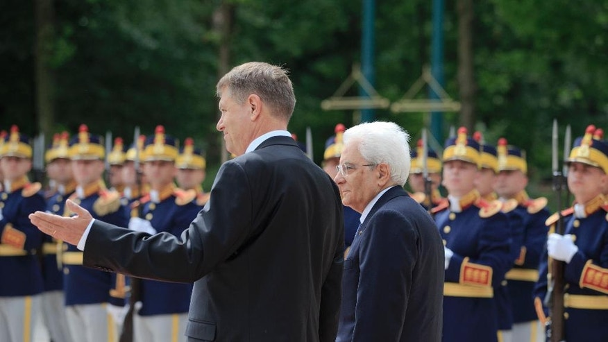Italy's President Sergio Mattarella, right, walks with Romanian counterpart Klaus Iohannis by the honor guard during the welcoming ceremony at the Cotroceni Presidential Palace in Bucharest, Romania, Tuesday, June 14, 2016. Mattarella is on an official visit to Romania. (AP Photo/Vadim Ghirda)