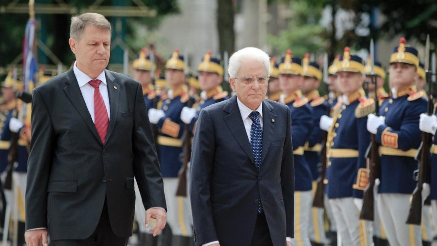 Italy's President Sergio Mattarella, right, walks with his Romanian counterpart Klaus Iohannis to review the honor guard during the welcoming ceremony at the Cotroceni Presidential Palace in Bucharest, Romania, Tuesday, June 14, 2016. Mattarella is on an official visit to Romania. (AP Photo/Vadim Ghirda)