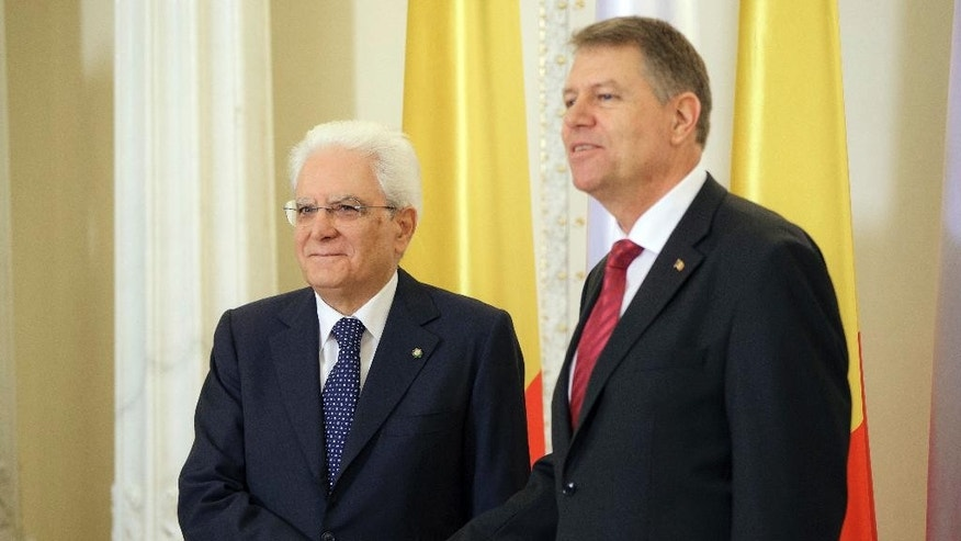 Italy's President Sergio Mattarella, left, shakes hands with his Romanian counterpart Klaus Iohannis during the welcoming ceremony at the Cotroceni Presidential Palace in Bucharest, Romania, Tuesday, June 14, 2016. Mattarella is on an official visit to Romania. (AP Photo/Vadim Ghirda)