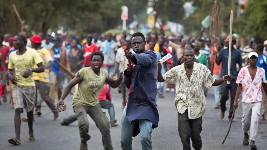 Opposition supporters carrying rocks and wooden sticks protest against a pro-government MP whom they allege made offensive remarks about the opposition leader, in the Kibera slum of Nairobi, Kenya Tuesday, June 14, 2016. The protesters threw rocks and engaged in running battles with riot police who fired teargas and chased them through the streets and alleys. (AP Photo/Ben Curtis)
