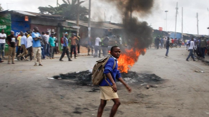 A schoolboy walks past a burning barricade set up by opposition supporters in protest over a pro-government MP whom they allege made offensive remarks about the opposition leader, in the Kibera slum of Nairobi, Kenya Tuesday, June 14, 2016. The protesters then threw rocks and engaged in running battles with police who fired teargas and chased them through the streets and alleys. (AP Photo/Khalil Senosi)