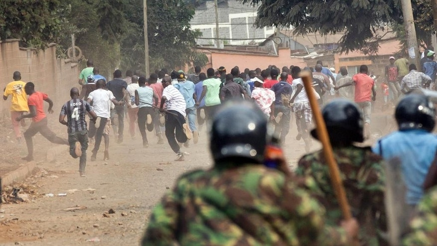 Kenyan riot police charge opposition protesters demonstrating against a pro-government MP whom they allege made offensive remarks about the opposition leader, in the Kibera slum of Nairobi, Kenya Tuesday, June 14, 2016. The protesters threw rocks and engaged in running battles with riot police who fired teargas and chased them through the streets and alleys. (AP Photo/Ben Curtis)