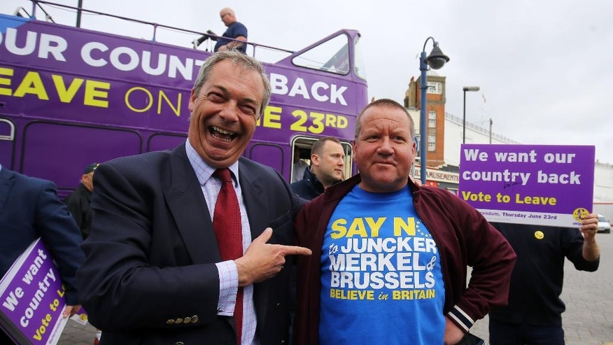Ukip leader Nigel Farage, left,  poses with local Ramsgate taxi driver Chris Bissett  during his party's referendum bus tour in Thanet, Kent, England, Monday June 13, 2016. Polls suggest the June 23 vote on whether to leave the 28-nation bloc could go either way. (Gareth Fuller/PA Photos via AP) UNITED KINGDOM OUT