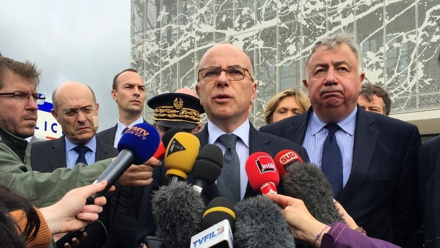 French Interior Minister Bernard Cazeneuve answers reporters after visiting the police station in Les Mureaux, west of Paris, Tuesday, June 14, 2016. A 25-year-old Frenchman with a past terrorist conviction is suspected in Monday's killing of two police officials  in the Paris suburb of Magnanville. (AP Photo/Nadine Achoui-Lesage)