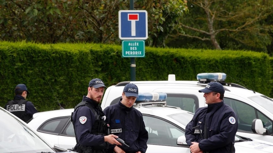 French police officers block the road leading to a crime scene the day after a knife-wielding attacker stabbed a senior police officer to death Monday evening outside his home in Magnanville, west of Paris, France, Tuesday, June 14, 2016. The attacker and a female companion of the police commander were later found dead after police commandos stormed the home and rescued the couple's three-year-old son. (AP Photo/Thibault Camus)