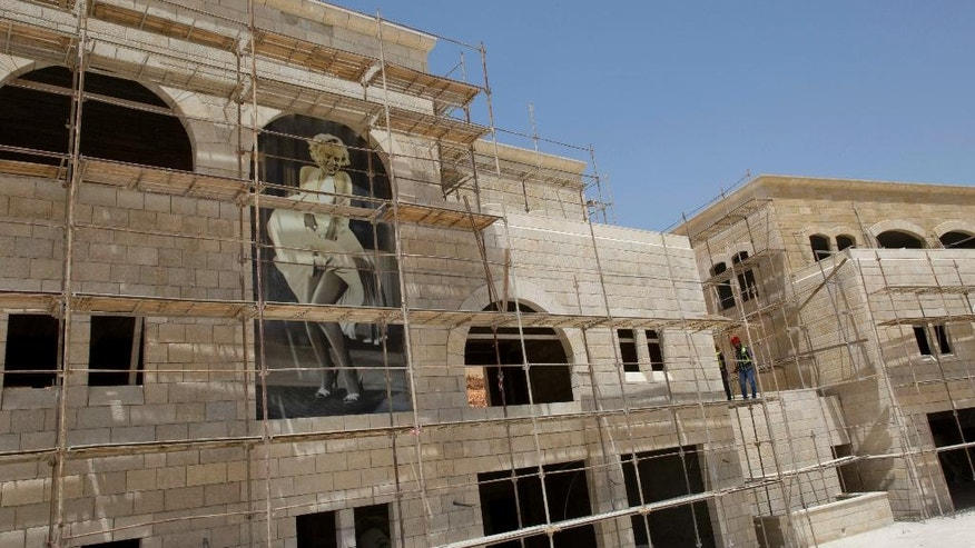 In this June 4, 2016 photo, a image of American actress Marilyn Monroe decorates an entertainment complex building under construction, in the West Bank city of Rawabi, north of Ramallah. After years of setbacks, Palestinians are starting to move into their first planned city being built in the West Bank -- a move that isn't just about real estate but also a symbol of their aspirations for statehood after nearly 50 years of Israeli military occupation. Though Rawabi is years from being finished, the city is a rare source of pride and excitement for the territory at a time of growing malaise over a standstill in Mideast peace efforts. (AP Photo/Nasser Nasser)