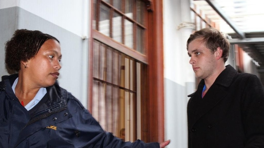 Henri van Breda, right, is led by a South African police woman as he arrives at the Stellenbosch magistrate court in Stellenbosch, South Africa, Tuesday June 14, 2016. The 21-year-old man who faces three counts of murder for the ax killings of his parents and older brother was released on $6,500 bail Tuesday, a day after he turned himself in to police. (AP Photo/Danie Keet, Eikestadnuus)