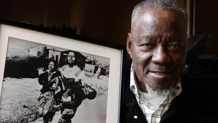 FILE - In this April 27, 2011 file photo South African photographer, Sam Nzima, poses with his iconic photo showing 13-year-old Hector Pieterson, being carried after being shot by police during the 1976 Soweto uprising. The day was a key moment in the long campaign to end South Africa's harsh apartheid system of white-minority rule. Forty years ago, black students in Johannesburg's Soweto township marched in protest and some were gunned down by police, appalling the world. (AP Photo/Denis Farrell, File)