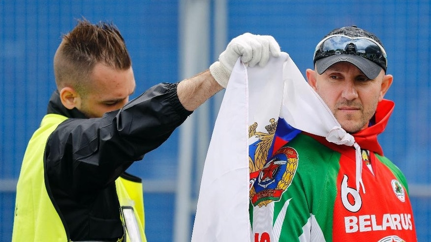 A steward checks the flag of a russian supporter at the stadium entrance prior to the Euro 2016 Group B soccer match between Russia and Slovakia at the Pierre Mauroy stadium in Villeneuve d'Ascq, near Lille, France, Wednesday, June 15, 2016. (AP Photo/Frank Augstein)