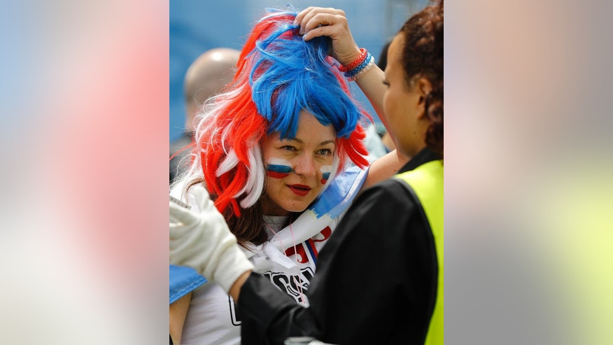 A supporter takes off her wig in team colors as she is searched by a steward at the stadium entrance prior to the Euro 2016 Group B soccer match between Russia and Slovakia at the Pierre Mauroy stadium in Villeneuve d'Ascq, near Lille, France, Wednesday, June 15, 2016. (AP Photo/Frank Augstein)