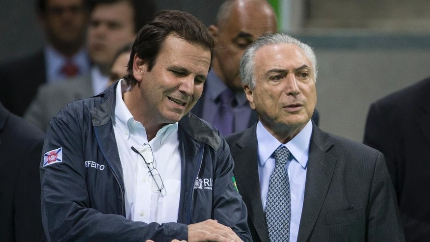 Brazil's interim President Michel Temer, right, talks to Rio de Janeiro Mayor Eduardo Paes as they visit Olympic Park in Rio de Janeiro, Brazil, Tuesday, June 14, 2016. In recent weeks Temer has stepped up his pledges of support for Rio games, which have been beset by a series of problems including the ongoing political crisis, Brazil's worst recession in decades and an outbreak of the Zika virus, which has been linked to birth defects in infants. (AP Photo/Felipe Dana)