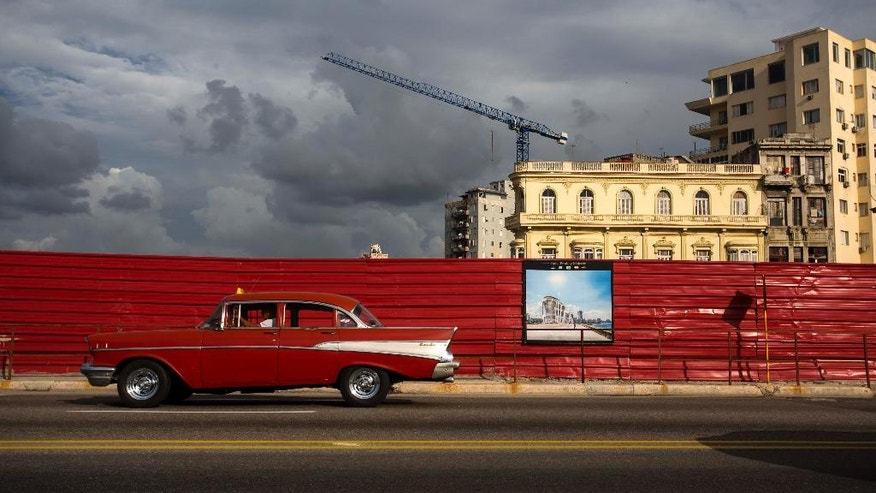 In this June 9, 2016 photo, a classic American car drives past an empty lot where a hotel is projected to be built along the Malecon sea wall in Havana, Cuba. A year and a half into normalization with the U.S., Cuba faces either an exciting new era of foreign investment or another in a string of false starts. (AP Photo/Desmond Boylan)