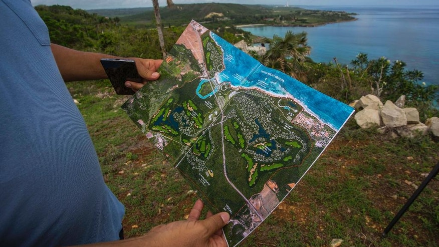 """In this June 10, 2016 photo, Guy Chartier, president of Wilton Properties Ltd. and project head of Montreal-based developer 360 VOX, shows the map of luxury hotels and a golf course projected to be built on the site where he's standing in Jibacoa, Cuba. """"One thing you need to have here is patience,"""" Chartier said. """"Companies shouldn't come to Cuba if they don't have a long-term view."""" (AP Photo/Desmond Boylan)"""