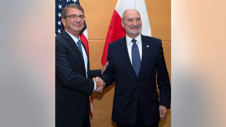 Polish Defense Minister Antoni Macierewicz, right, is greeted by U.S. Secretary of Defense Ash Carter prior to a meeting at NATO headquarters in Brussels on Wednesday, June 15, 2016. NATO concludes a two-day meeting on Wednesday with discussions on the situation in Afghanistan and Ukraine. (AP Photo/Virginia Mayo, Pool)