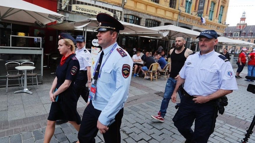 Russian police officers walk through a square in downtown Lille, Wednesday, June 15, 2016 after being called into to bolster security ahead of the Euro 2016 Group B soccer match between Russia and Slovakia at the Pierre Mauroy stadium in Villeneuve d'Ascq, near Lille. UEFA gave Russia a suspended disqualification from the tournament after violence at their previous match against England in Marseille. (AP Photo/Darko Bandic)