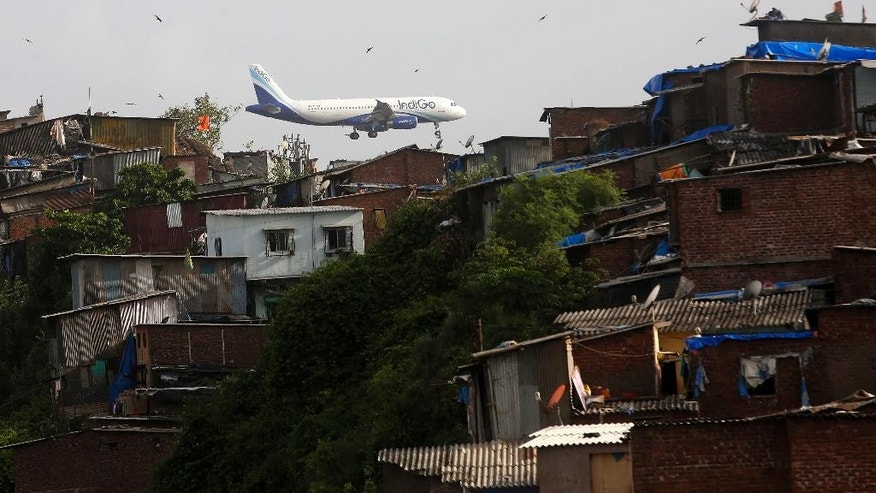 An aircraft of India's private airline Indigo flies above shanties adjacent to the Chhatrapati Shivaji airport as it prepares to land in Mumbai, India, Wednesday, June 15, 2016. India's government on Wednesday approved a new civil aviation policy aimed at increasing regional connectivity, boosting cargo operations and making it easier — and possibly cheaper — for passengers to fly. (AP Photo/ Rajanish Kakade)