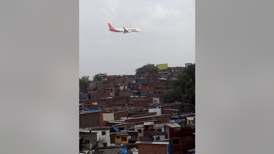 An aircraft of India's private airline Spicejet flies above shanties adjacent to the Chhatrapati Shivaji airport as it prepares to land in Mumbai, India, Wednesday, June 15, 2016. India's government on Wednesday approved a new civil aviation policy aimed at increasing regional connectivity, boosting cargo operations and making it easier — and possibly cheaper — for passengers to fly. (AP Photo/ Rajanish Kakade)