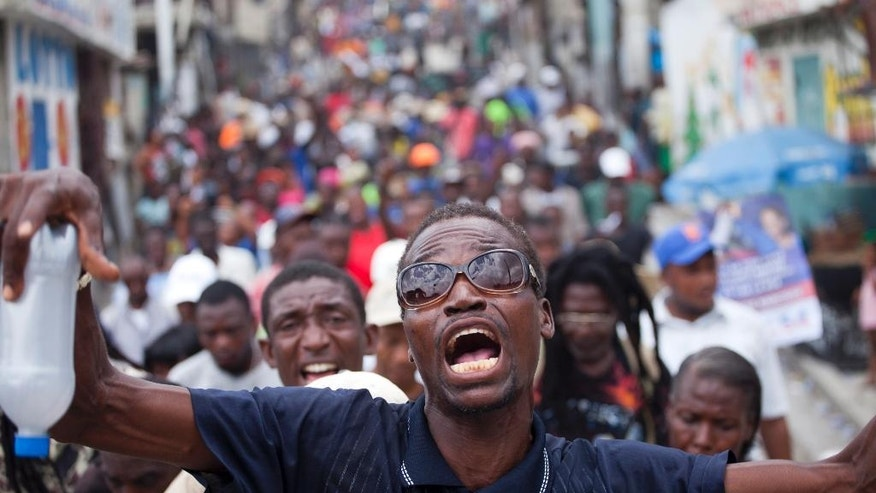 Supporters of presidential candidate Maryse Narcisse chant slogans against legislators as they march to the parliament building during a demonstration in support of interim President Jocelerme Privert, in Port-au-Prince, Haiti, Tuesday, June 14, 2016. Haiti's legislators will decide whether to pave way for a new interim leader until elections can be resolved or extend the term for Privert, whose 120-day mandate is due to expire today. ( AP Photo/Dieu Nalio Chery)
