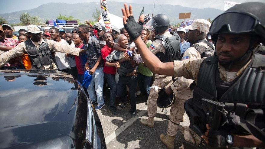Police keep supporters of presidential candidate Maryse Narcisse from stopping a car from crossing the entrance into the parliament building during a demonstration in support of interim President Jocelerme Privert, in Port-au-Prince, Haiti, Tuesday, June 14, 2016. Haiti's legislators will decide whether to pave way for a new interim leader until elections can be resolved or extend the term for Privert, whose 120-day mandate is due to expire today. ( AP Photo/Dieu Nalio Chery)