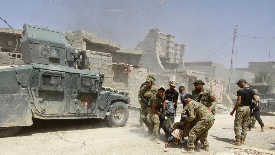 Iraqi security forces evacuate an injured soldier during heavy fighting against Islamic State group militants in Fallujah, Iraq, Wednesday, June 15, 2016. Fallujah has been locked in a cycle of conflict since 2003, when it emerged as a bastion of the insurgency against the Americans. Militant attacks and bombings were followed by sweeping arrest raids, which further stoked local grievances. In 2004, U.S. troops launched two massive assaults on the city, where they fought their bloodiest battles since Vietnam. (AP Photo/Anmar Khalil)
