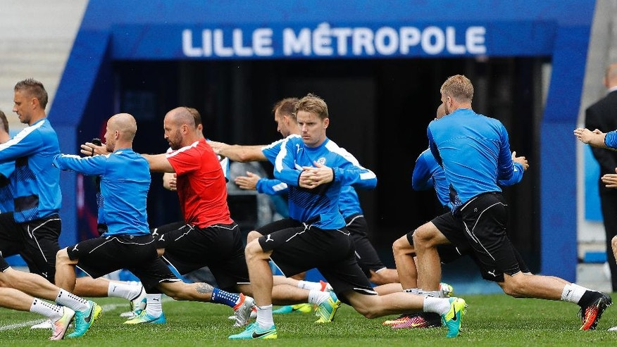 Slovakia teammates stretch during a training session at the Pierre Mauroy stadium in Villeneuve d'Ascq, near Lille, France, Tuesday, June 14, 2016. Slovakia faces Russia in a group B match on Wednesday June 15, 2016. (AP Photo/Frank Augstein)