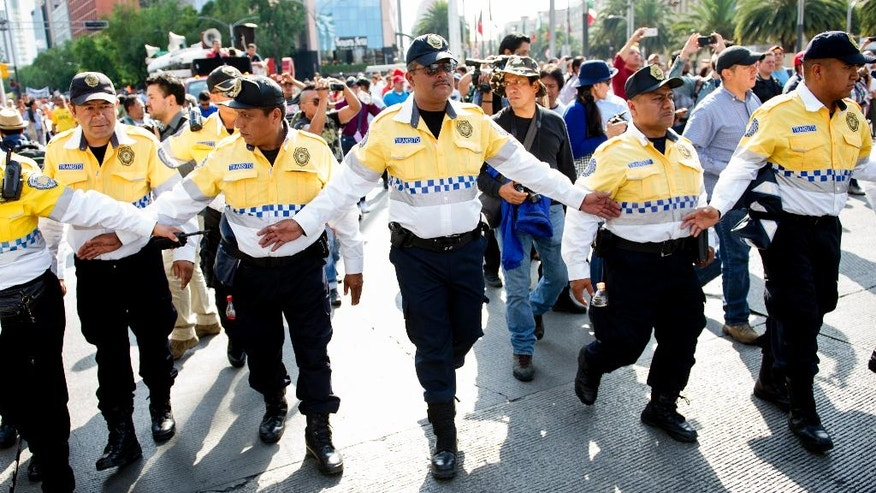 Mexico City transit police form a safety line as CNTE teachers union protestors advance along Paseo de la Reforma in Mexico City, Tuesday, June 14, 2016. The teachers union is striking against plans to overhaul the country's education system which include federally mandated teacher evaluations. (AP Photo/Nick Wagner)