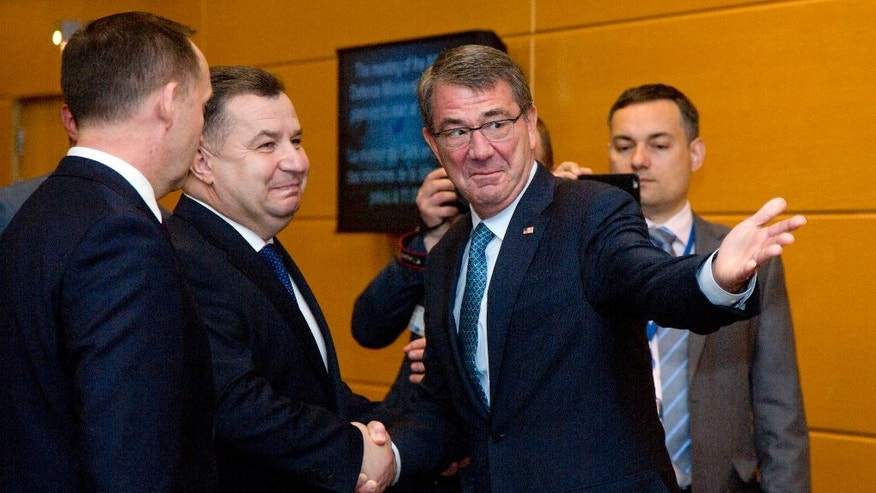 Ukraine's Defense Minister Stepan Poltorak, second left, is greeted by U.S. Secretary of Defense Ash Carter, second right, prior to a meeting at NATO headquarters in Brussels on Wednesday, June 15, 2016. NATO concludes a two-day meeting on Wednesday with discussions on the situation in Afghanistan and Ukraine. (AP Photo/Virginia Mayo, Pool)