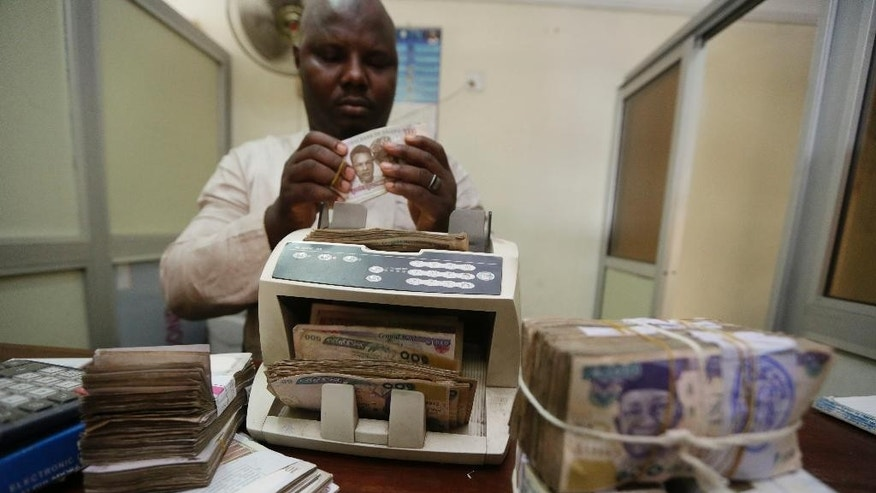 "FILE- In this Tuesday Oct. 20, 2015 file photo, a money changer counts Nigerian naira currency at a bureau de change, in Lagos Nigeria. Nigeria will float its embattled naira currency, the Central Bank governor announced Wednesday, June 15, 2016 after months of pressure to control a spiraling crisis in Africa's biggest economy. Gov. Godwin Emefiele told reporters the naira rate will be ""market-driven"" from June 20. (AP Photo/Sunday Alamba, File)"