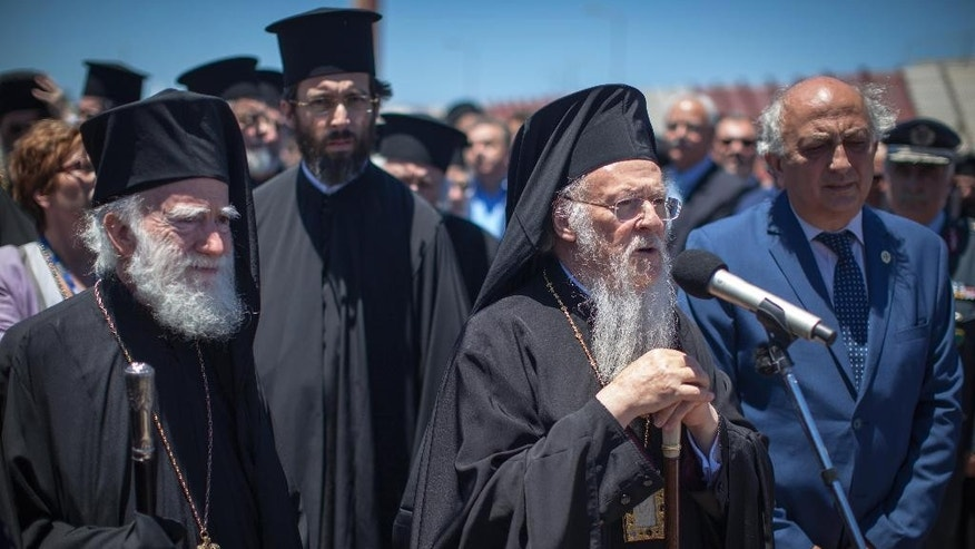 In this Wednesday, June 15, 2016 photo released by Holy and Great Council, Ecumenical Patriarch Bartholemew, centre, speaks next to Archbishop of Crete Irineos, left, and Deputy Greek Foreign Minister Yannis Amanatides, during his arrival at the airport of Chania in the Greek island of Crete. The spiritual leader of the world's Orthodox Christians on Wednesday said a historic meeting of church leaders _ the first in more than a millennium _ will to take place despite a pullout by Russia, the fourth Orthodox church to say it won't attend the June gathering in Crete.  (Holy and Great Council via AP)