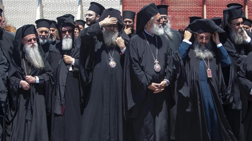 In this Wednesday, June 15, 2016 photo released by Holy and Great Council, Senior Orthodox clergy wait the arrival of Ecumenical Patriarch Bartholmew I at the airport of Chania in the Greek island of Crete. Bartholmew I , the spiritual leader of the world's Orthodox Christians on Wednesday said a historic meeting of church leaders — the first in more than a millennium — will take place despite a pullout by Russia, the fourth Orthodox church to say it won't attend the June gathering in Crete. (Holy and Great Council via AP)