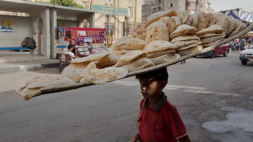 An Egyptian bread vendor looks for clients at a market in the neighborhood of Sayeda Zeinab, in Cairo, Egypt, Tuesday, June 14, 2016. Price hikes in Egypt are taking much of the joy out of Ramadan, the Muslim holy month when families traditionally break the dawn-to-dusk fast with lavish feasts. Annual inflation hit 12.23 percent in May, the highest level in seven years, and the economy has yet to recover from the 2011 uprising that toppled Hosni Mubarak. (AP Photo/Amr Nabil)