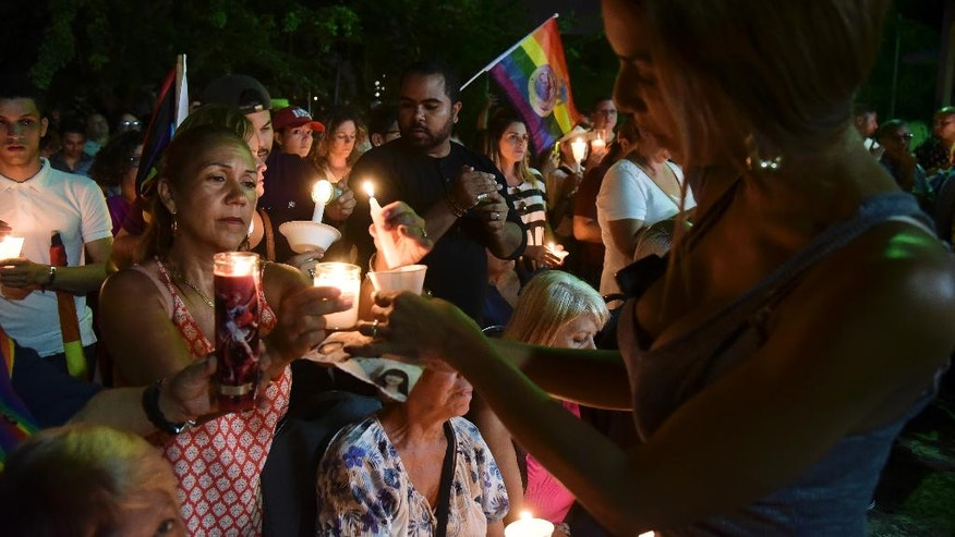 Residents carry out a vigil to honor the memory of the Puerto Ricans that died in the mass shooting at a nightclub in Orlando, Fla., at the Hato Rey LGBTT Community Center in San Juan, Puerto Rico, Tuesday, June 14, 2016. Dozens of people died at the 'Pulse' gay nightclub in Orlando, making it the deadliest mass shooting in modern U.S. history. (AP Photo/Carlos Giusti)