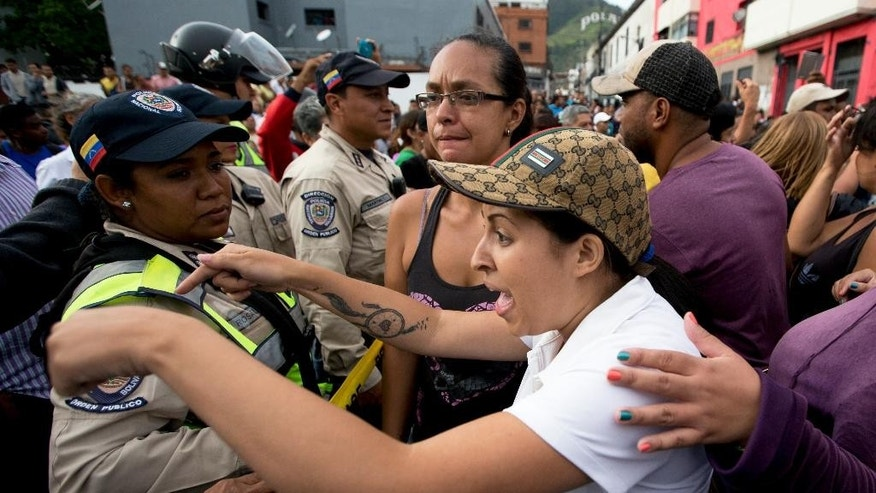 A woman argues with the police during a protest for food at the Catia neighborhood in Caracas, Venezuela, Tuesday, June 14, 2016. Tensions rose after customers waited in line for hours and their frustration turned into a street protest. (AP Photo/Fernando Llano)