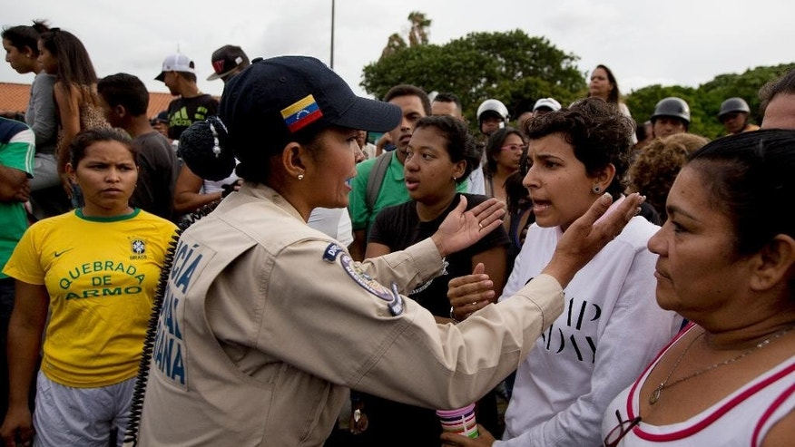 A police officer talks to an angry crowd during a protest for food at the Catia neighborhood in Caracas, Venezuela, Tuesday, June 14, 2016. Tensions rose after customers waited in line for hours and their frustration turned into a street protest. (AP Photo/Fernando Llano)