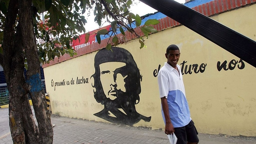 CARACAS, VENEZUELA - DECEMBER 02:  A Venezuelan walks past grafitti of revolutionary figure Che Guevara December 2, 2006 in Caracas, Venezuela. President Hugo Chavez faces challenger Manuel Rosales in the presidential elections December 3.  (Photo by Mario Tama/Getty Images)