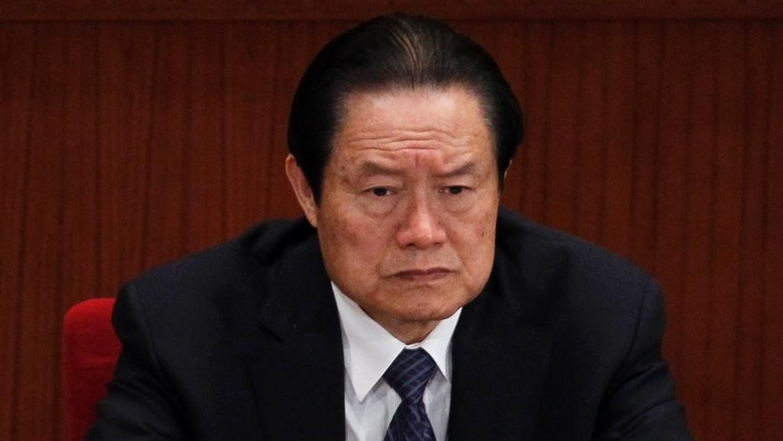 FILE - In this March 9, 2012, file photo, Zhou Yongkang, then Chinese Communist Party Politburo Standing Committee member in charge of security, attends a plenary session of the National People's Congress at the Great Hall of the People in Beijing. A Chinese court on Wednesday, June 15, 2016,  jailed the wife and a son of Zhou, a former senior politician sentenced to life in prison a year ago for corruption amid an ongoing anti-graft campaign. The fall of Zhou and his family is one of most powerful examples in recent years of how families of Chinese politicians who used their positions to enrich themselves can fall spectacularly once their power has dissipated. (AP Photo/Ng Han Guan, File)