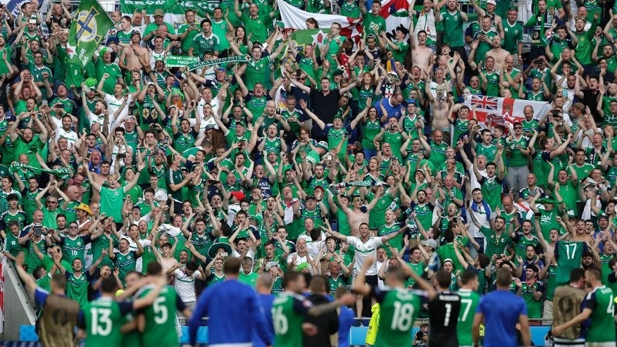 Northern Ireland supporters celebrate with the players, in the foreground, at the end of the Euro 2016 Group C soccer match between Ukraine and Northern Ireland at the Grand Stade in Decines-­Charpieu, near Lyon, France, Thursday, June 16, 2016. Northern Ireland won 2-0. (AP Photo/Pavel Golovkin)